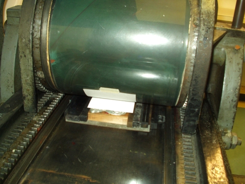a piece of newsprint the same size as the paper to be printed on is placed in position on the plates and the drum is rolled across until it grabs the paper.